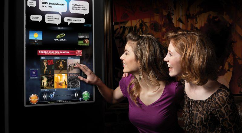 Two happy customers using an E-case touch screen kiosk in a bar